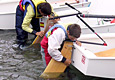 Children try to align the rudder pins with the boat's rocking transom